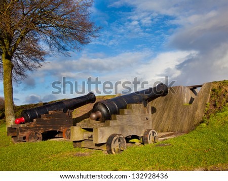 Two Old Cannons Behind a Dam in the Museum Fortress of Bourtange in the Netherlands