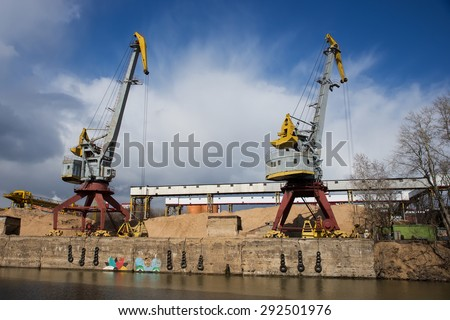 Two old crane loading cargo in the river port, moscow river - stock photo