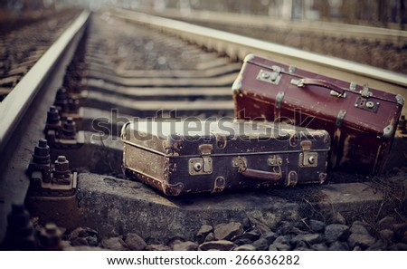 Two old fashioned forgotten a suitcases lie on railway rails. - stock photo