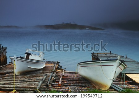 Two old fishing boat on the wooden bridge in misty weather - stock photo