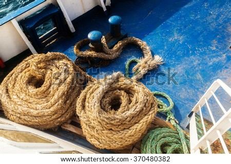 Two old fleecy ropes curtailed into a spiral on the deck of the vessel - stock photo