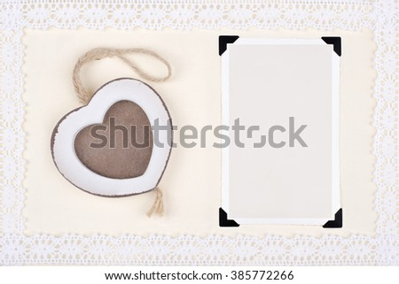 Two old photo frames (one in wood heart shape) on decorative paper framed with lace. - stock photo