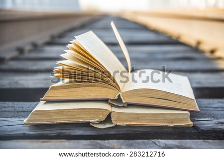 Two old retro vintage aged used book lie on wooden sleepers of railway between metal fence of grunge style bridge on blue sky background Education development cultivation symbol sign concept  - stock photo