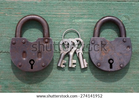 two Old rusty padlock and key on wood background