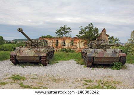 Two old tank in front of ruined brick building  - stock photo