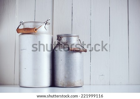 Two old vintage aluminum milk cans, painted white wooden board, rustic background - stock photo