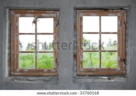 Two old windows, concrete wall and split glass - stock photo