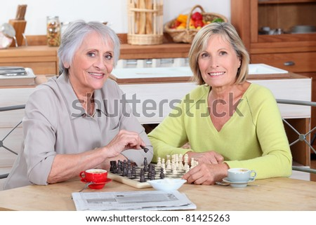 Two old women playing chess in kitchen