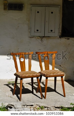two old wooden chairs are standing close on an old porch - stock photo