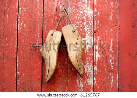 two old wooden shoe lasts hanging on red wall - stock photo