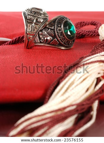 two older class rings sitting on graduation cap and diploma - stock photo