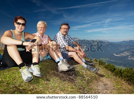 Two older parents with their daughter on top of a mountain - stock photo