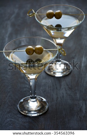 Two olive martini cocktails on dark wooden background - stock photo