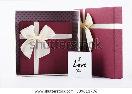 "Two open gift box with yellow ribbon with red heart shape gift box inside with ""I Love You"" words on white card - anniversary, valentine, birthday and couple concept - stock photo"