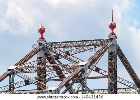 Two ornate red finials grace the top of this aged cantilever bridge spanning the Ohio River near Wheeling, West Virginia. Sadly, this bridge is scheduled for demolition. - stock photo