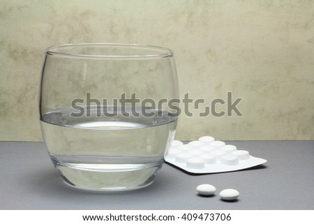 Two painkiller tablets from a blister pack with a glass of water - stock photo