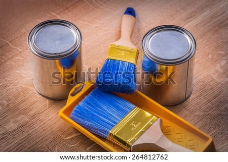 two paint cans brushes tray on wooden board construction concept  - stock photo