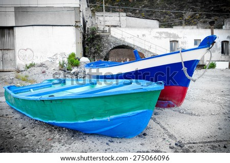 Two painted old boats somewhere on the coast of Sicily, Italy - stock photo