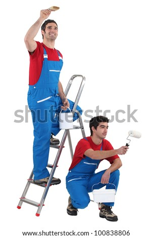 Two painter working on the same house - stock photo