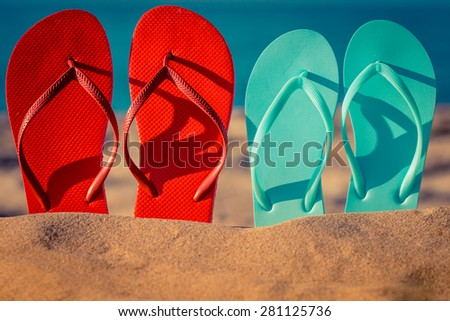 Two pair flip-flops on the sand. Summer vacation concept