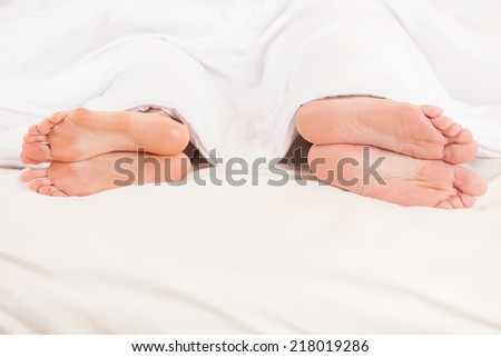 Two pair of feet far from each other in bed. Closeup of four feet in bed lying
