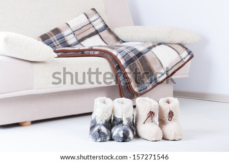 Two pair of natural woollen slippers on wooden floor and blanket on the couch - stock photo