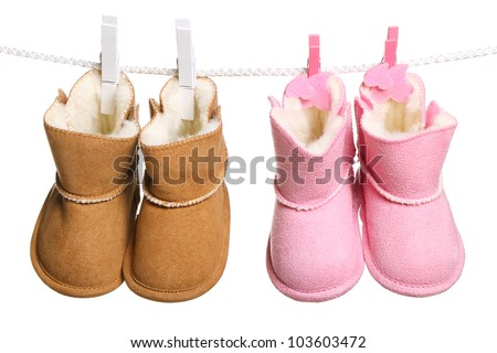 Two pair of winter boots hanging on the clothesline. Image isolated on white background - stock photo