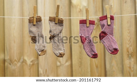 Two pair off child socks are hanging at the clothesline in the sun - stock photo