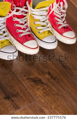 two pairs of cool youth red and yellow  gym shoes white laces   on brown wooden floor  standing in line with copy place   - stock photo