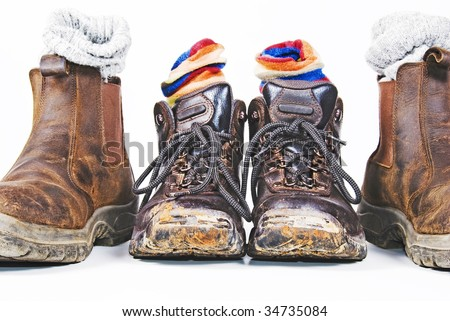 Two pairs of dirty hiking boots and socks - stock photo
