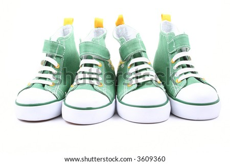 two pairs of green sneakers for children isolated on white