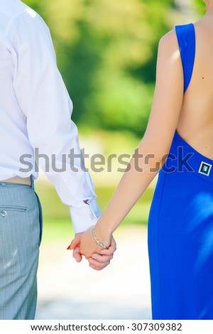 two pairs of hands in love tenderly hold together . Park . Outdoor . - stock photo