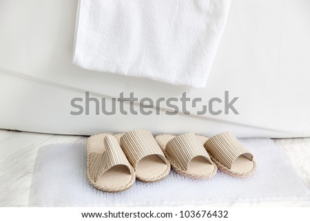 Two pairs of slippers on  bath mat by  the bathtub with towel, a pair for man and another for woman. - stock photo