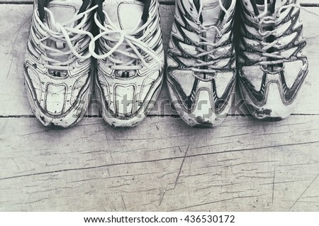 two pairs of white sports shoes on a wooden background, vintage toning