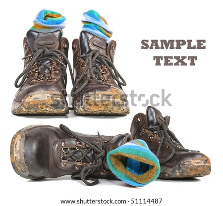 Two pairs of worn hiking boots still with mud on - stock photo