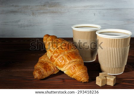Two paper cups of coffee, two croissants and three pieces of brown loaf-sugar on wooden background - stock photo