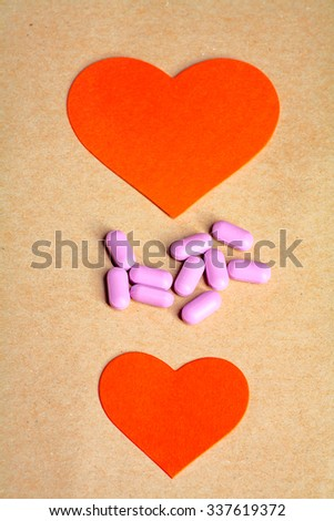 Two paper hearts and heart pills in the center vertical image. Heart health concept.  - stock photo