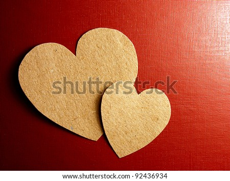 Two paper hearts over red textured paper - stock photo