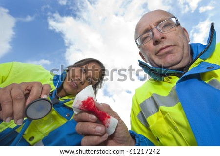 Two paramedics caring for a patient, seen from the patients point of view - stock photo