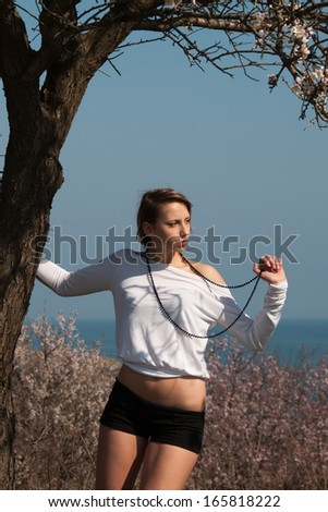 Two part outfit, Resting under a blossoming almond tree whilst gazing in the distance - stock photo