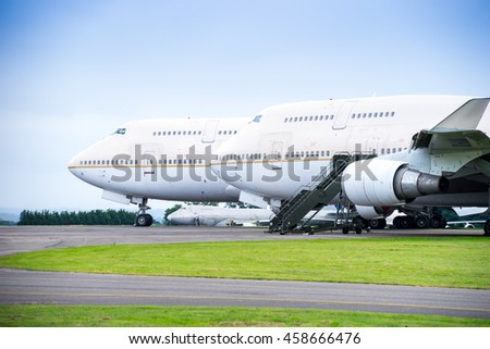 Two passenger airliners parked side by side on airport apron with engines removed for service, facing left - stock photo