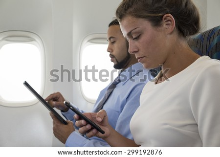 Two passengers using technology on a plane - stock photo