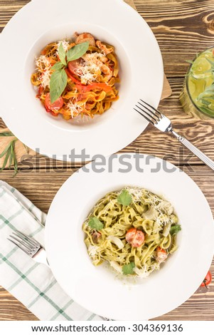Two pasta fettuccine with lemonade on wooden table - stock photo
