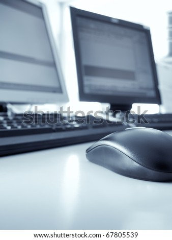 two PCs in the office, selective focus on the mouse, blue toned, for business or computer  themes