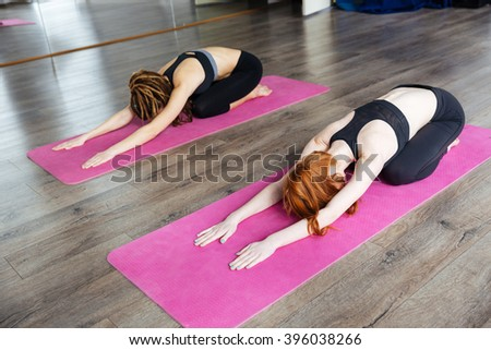 Two peaceful young woman relaxing and practicing yoga in studio - stock photo
