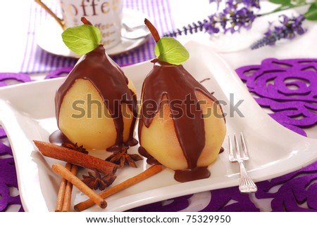 two pears poached in syrup poured chocolate sauce - stock photo