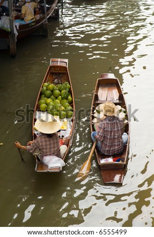 Two peasants in the boat sells their coconuts at at the floating market near Bangkok, Thailand. The floating market is in Damnoen Saduak near Bangkok, Thailand.