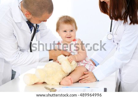Two pediatricians are taking care of baby in hospital. Little girl is being examining by doctor with stethoscope. Health care, insurance and help concept.
