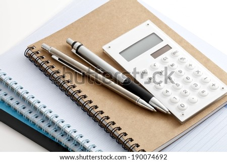 Two pens and a calculator sit on top of three notebooks. - stock photo