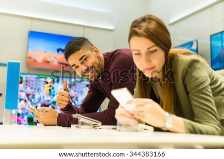 Two people are choosing smart phones. Woman is de-focused, man is in focus looking at camera holding thumb up. Shallow depth of field. - stock photo